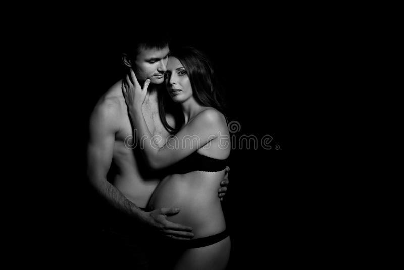 愉快的爱恋的夫妇单色画象立刻爱和柔软 移交怀孕的肚子妇女 库存照片
