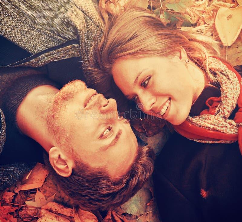 愉快的爱恋的夫妇说谎在秋叶的,特写镜头 免版税库存图片