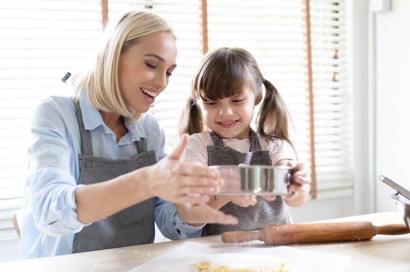 愉快的爱恋的家庭一起准备面包店 妈妈和一点逗人喜爱的女儿面团为烘烤做准备烹调曲奇饼和 免版税库存照片