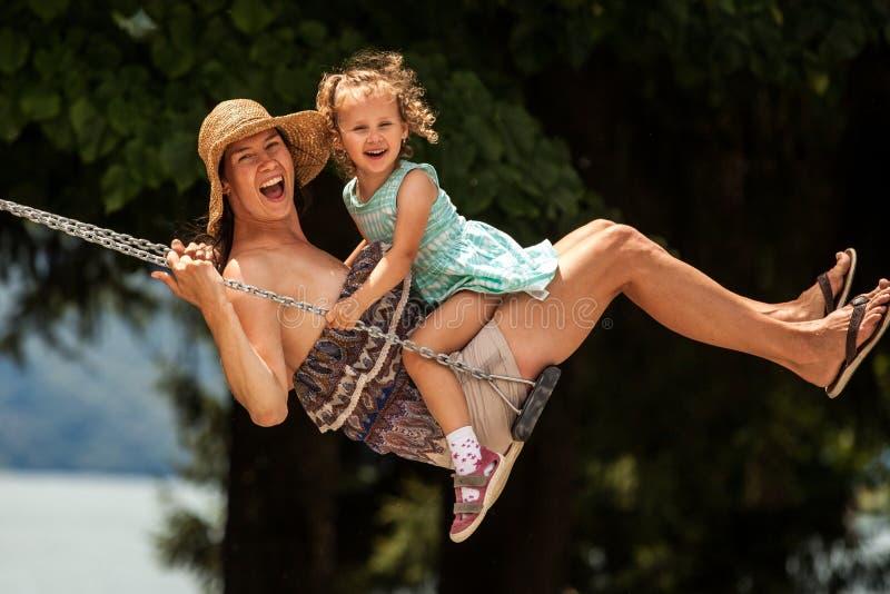 愉快的爱恋的家庭!年轻母亲和她的摇摆在摇摆和笑一个夏天晚上的儿童女儿户外,美丽 免版税库存图片