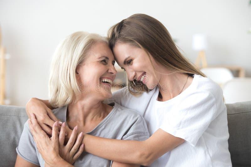 愉快的爱恋的更老的母亲和增长的千福年女儿笑 免版税库存照片