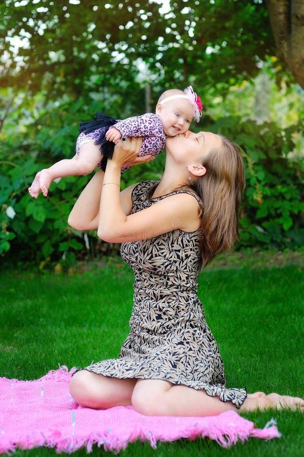 愉快的爱恋的母亲和她的婴孩画象户外 库存照片