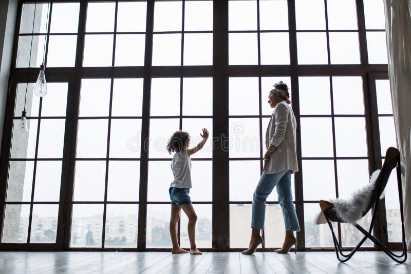 愉快的爱恋的美国黑人的家庭 年轻使用在托儿所的母亲和她的女儿 妈妈和女儿在跳舞 免版税库存图片