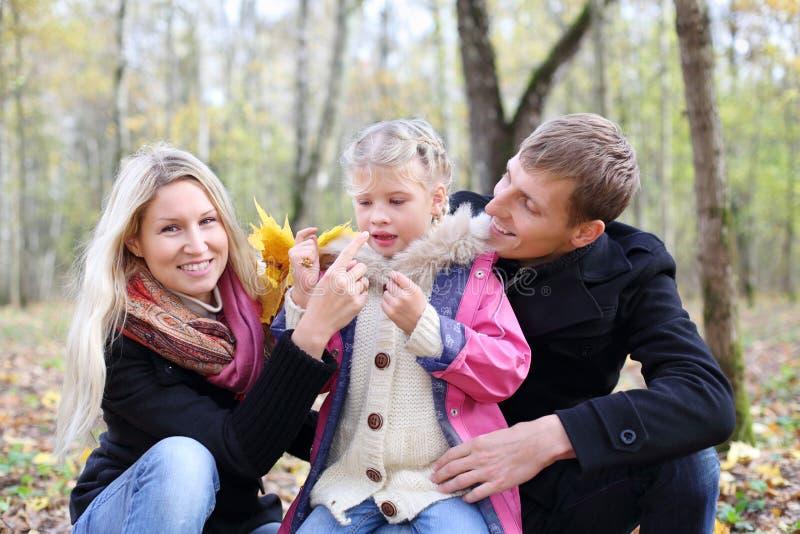 愉快的父亲、母亲和女儿有叶子的在秋天森林里 库存照片