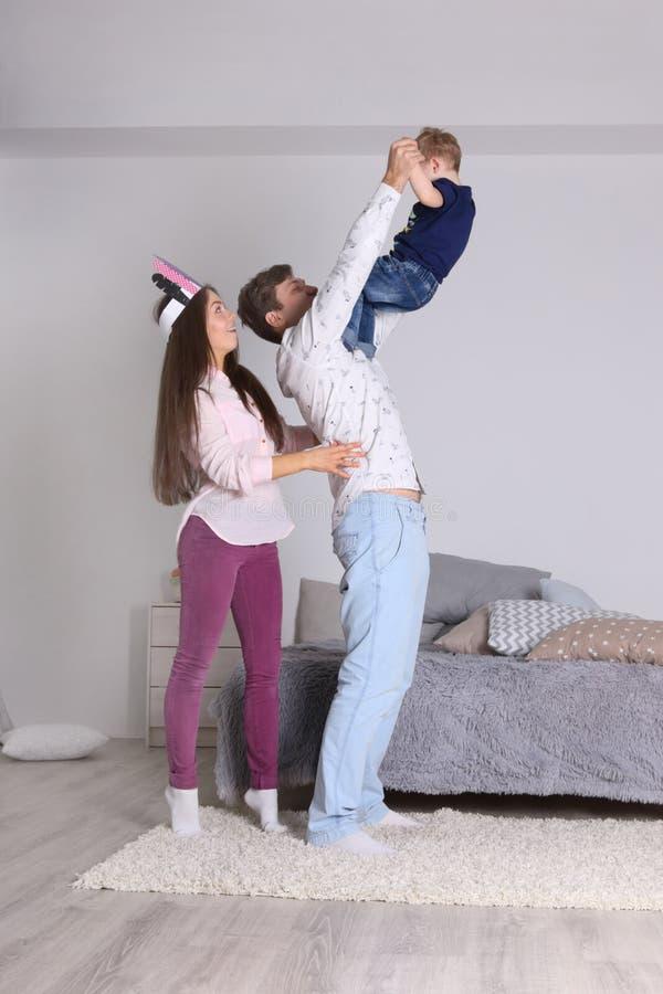 愉快的父亲、母亲和小儿子在床附近使用 免版税库存照片