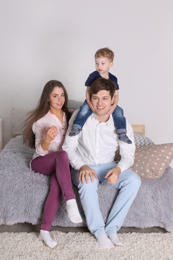 愉快的父亲、母亲和小儿子坐床 免版税库存照片