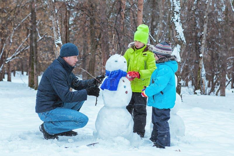 愉快的父亲和两个儿子在冬天公园铸造雪人 库存图片