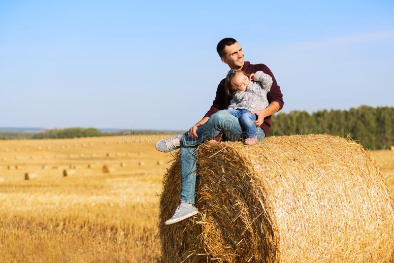 愉快的父亲和两岁的女孩坐在领域的干草捆 库存照片