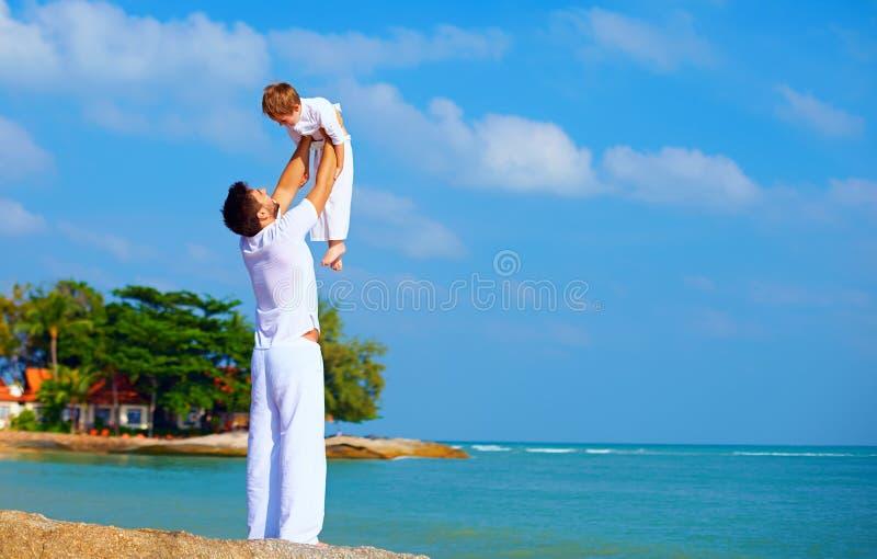 愉快的父亲和儿子享有在热带海岛上的生活 库存图片