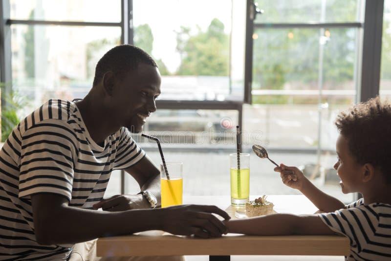 愉快的父亲和儿子咖啡馆的 免版税库存照片
