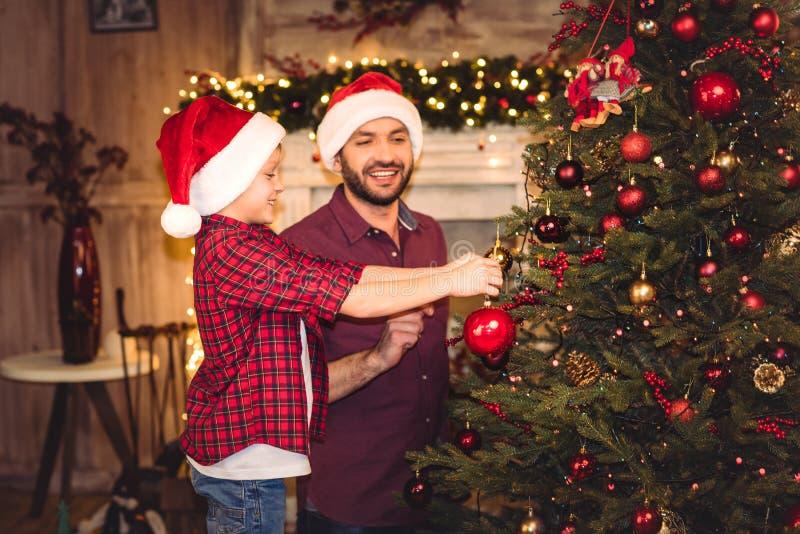 愉快的父亲和儿子圣诞老人帽子装饰的 图库摄影