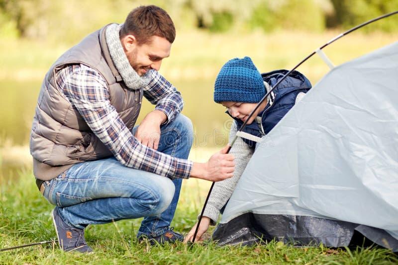 愉快的父亲和儿子安装帐篷户外 免版税库存照片