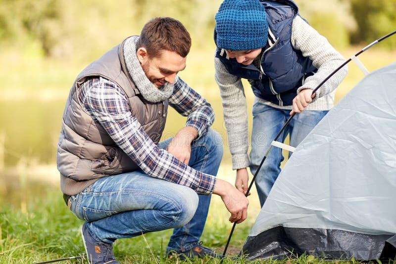愉快的父亲和儿子安装帐篷户外 库存图片