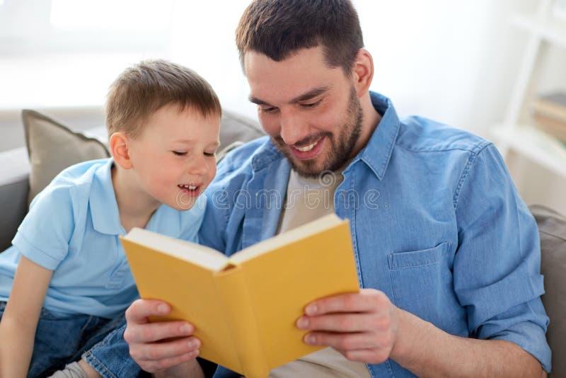 愉快的父亲和儿子阅读书沙发在家 免版税库存照片