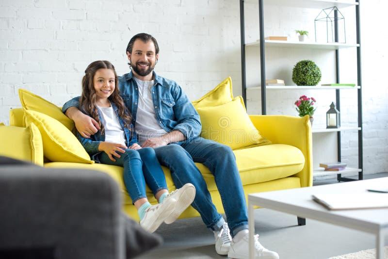 愉快的父亲和女儿一起坐黄色长沙发和微笑 图库摄影