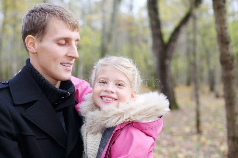 愉快的父亲和女儿在秋天森林里。 免版税库存图片