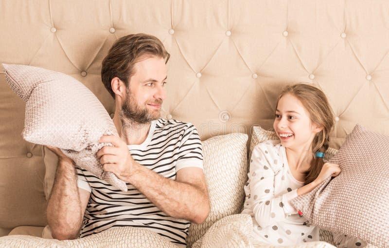愉快的父亲和女儿有枕头战在床 库存照片