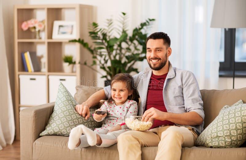愉快的父亲和女儿看着电视在家 免版税图库摄影