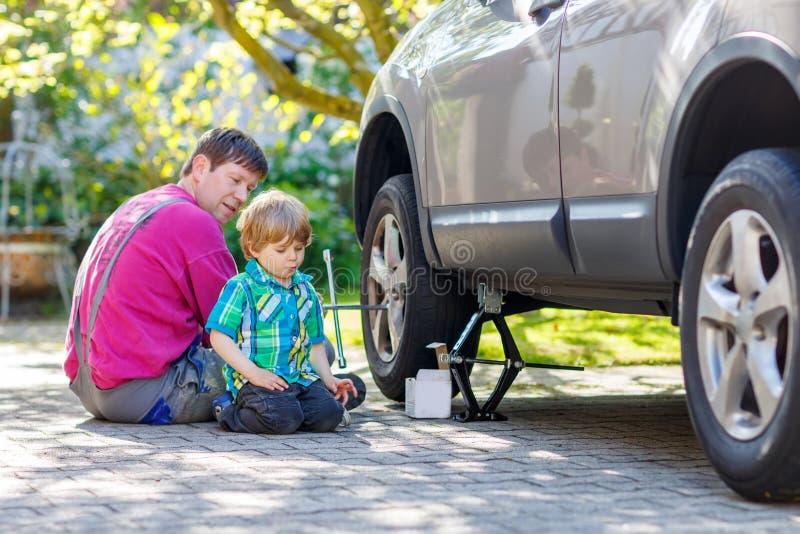 愉快的父亲和他的小修理汽车和樟宜的小孩男孩 免版税库存图片