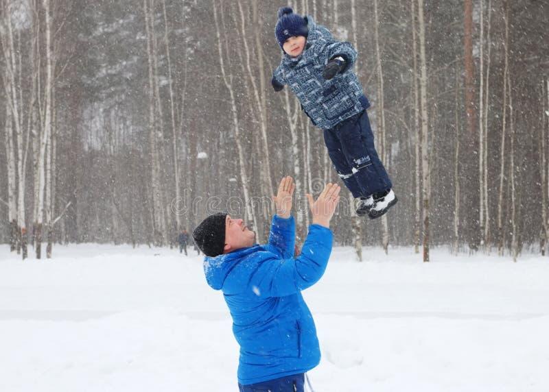 愉快的父亲在公园投掷她的年轻儿子 免版税库存照片