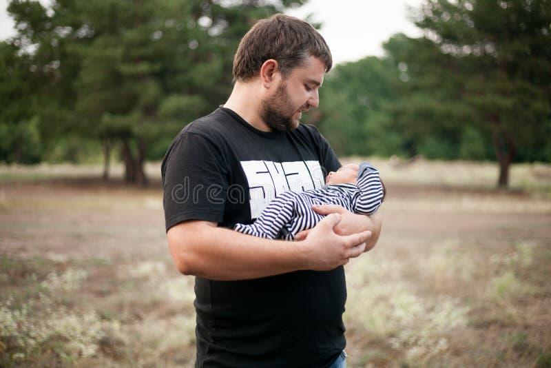 愉快的父亲在手上抱着他新出生的婴孩在步行 图库摄影