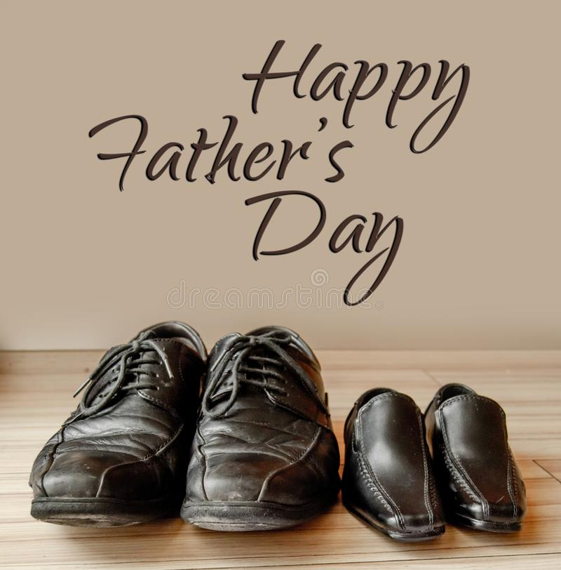 愉快的父亲节、父亲鞋子和男婴鞋子在头顶上,平的位置 库存图片