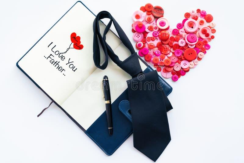 愉快的父亲节、红色按钮在心脏形状和黑暗的领带在书和豪华笔与文本我爱你生 库存图片