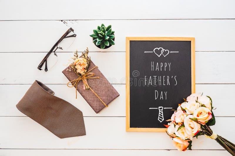 愉快的父亲节概念 礼物盒、领带、玻璃、玫瑰色花和笔记本的平的被放置的图象有愉快的父亲\'s天文本的 库存图片