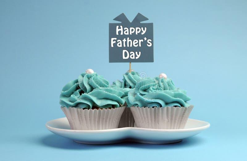 愉快的父亲节特别款待蓝色和白色美丽的装饰的杯形蛋糕 免版税库存照片