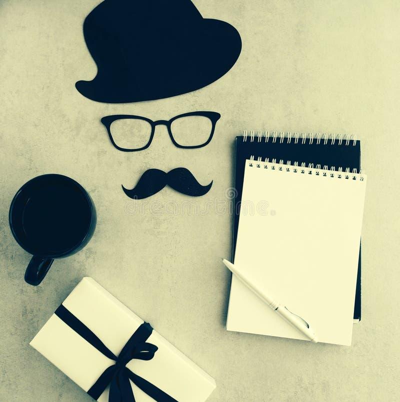 愉快的父亲节背景,卡片 滑稽的帽子、玻璃和髭、咖啡杯、gifr或者礼物,笔记本嘲笑 图库摄影