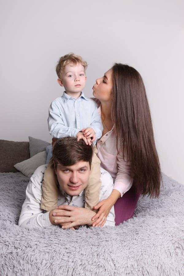 愉快的父亲,母亲,小儿子在灰色床上说谎 免版税库存图片