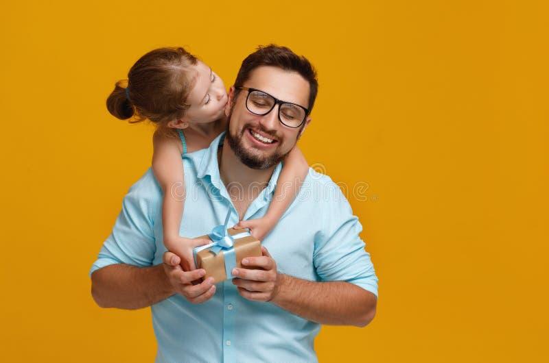 愉快的父亲` s天!逗人喜爱的拥抱在黄色后面的爸爸和女儿 库存照片