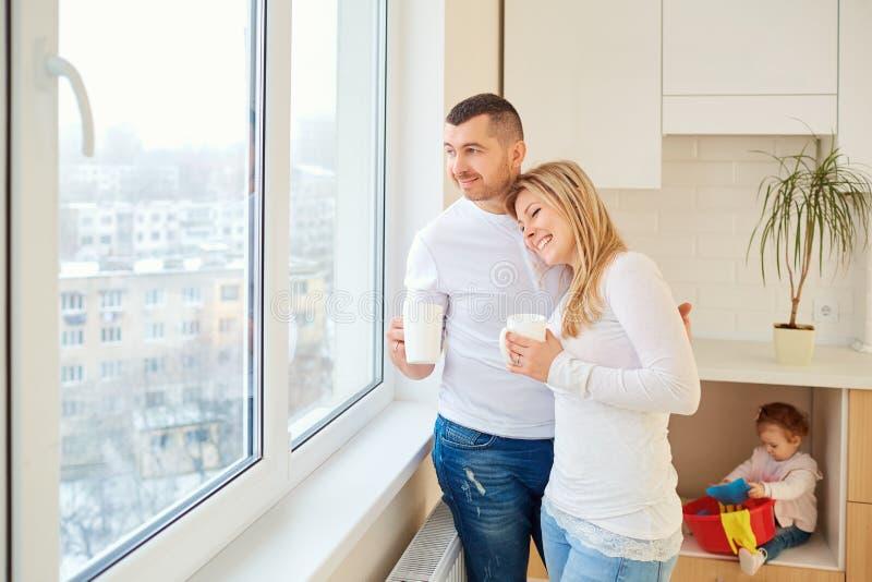 愉快的父母一起拥抱在窗口 免版税图库摄影