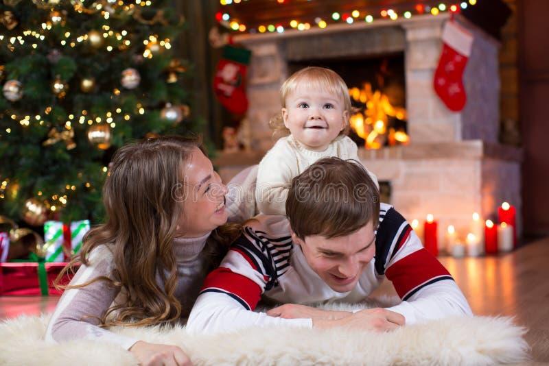 愉快的父母和儿童游戏在圣诞树附近在家 一起庆祝新年的父亲、母亲和儿子 免版税库存图片