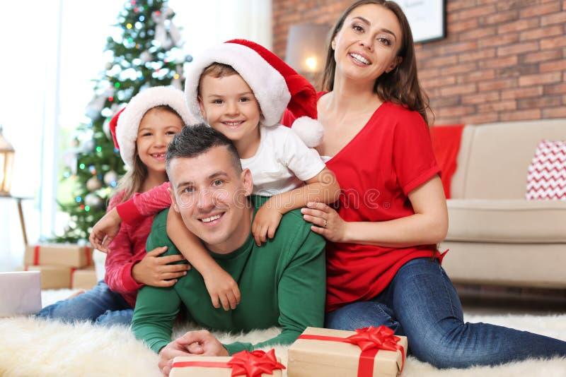 愉快的父母和孩子临近圣诞树 免版税库存照片