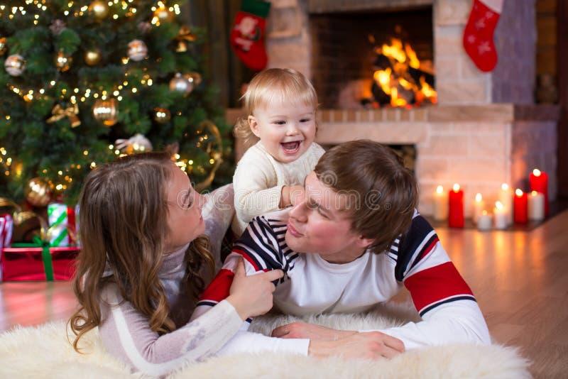 愉快的父母和孩子在家获得一个乐趣在圣诞树附近 一起庆祝新年的父亲、母亲和儿子 图库摄影