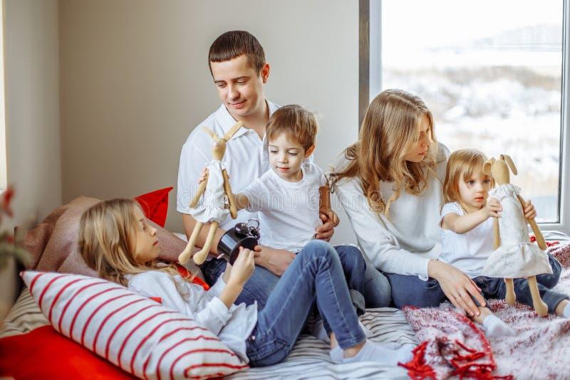愉快的父母和孩子在床上的享受他们的早晨 免版税库存照片