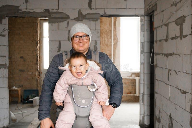 愉快的爸爸和婴孩载体的在新房里整修阶段的,泡沫混凝土,新的家背景  免版税库存照片