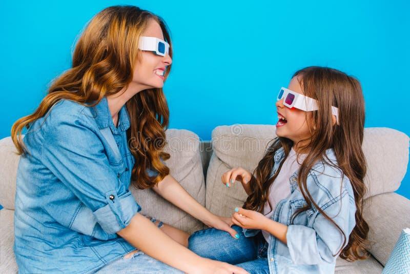 愉快的牛仔裤衣裳的互相微笑在长沙发的母亲和她的小女儿在蓝色背景 库存照片