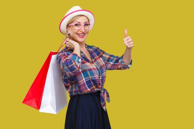 愉快的现代年迈的妇女白色帽子的和方格的衬衣身分的,拿着购物带来和显示与暴牙的赞许 免版税库存照片
