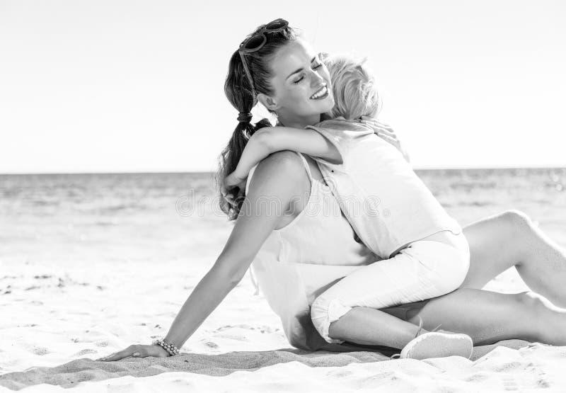 愉快的现代母亲和女儿海滩拥抱的 库存照片