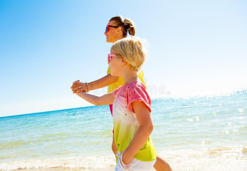 愉快的现代母亲和孩子海滨走的 免版税库存照片