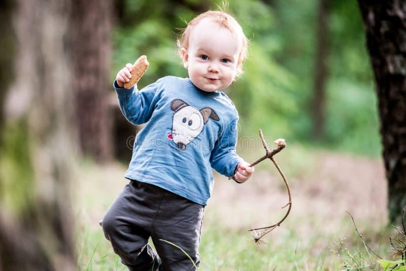 愉快的甜小孩在森林里 免版税图库摄影