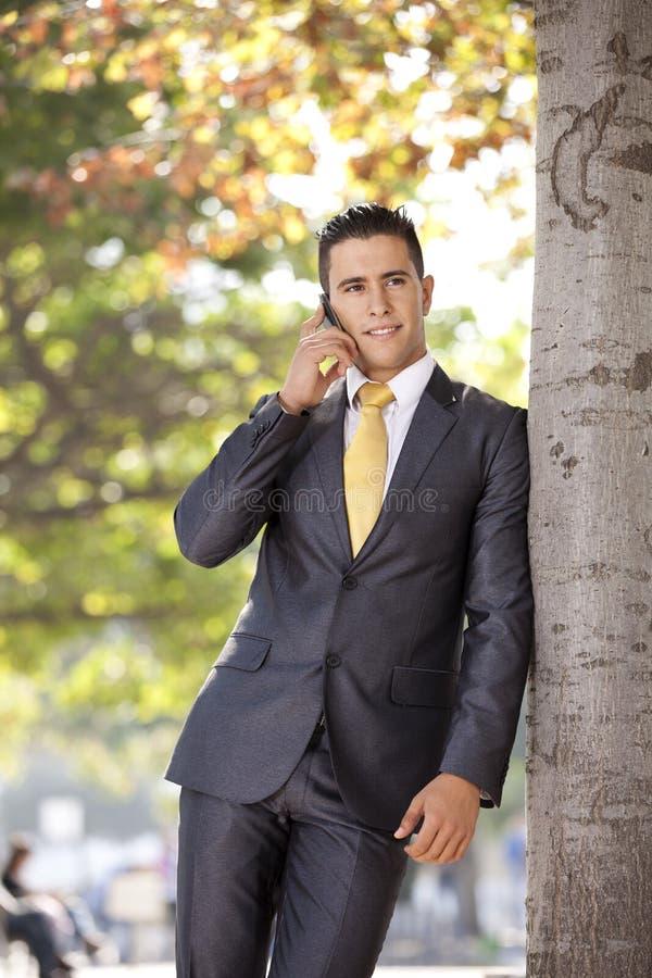 愉快的生意人联系在他的移动电话 库存照片