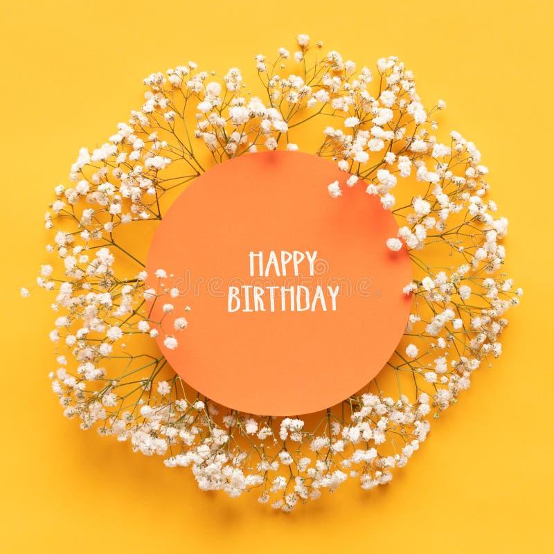愉快的生日贺卡 与美丽的矮小的白花的平的被放置的贺卡在明亮的黄色纸背景 免版税图库摄影