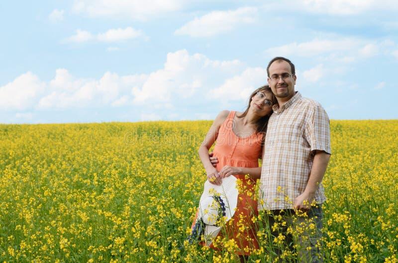 愉快的男人和妇女在黄色草甸 库存图片