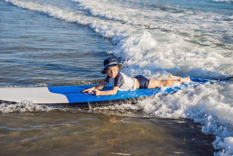愉快的男婴-在冲浪板的年轻冲浪者乘驾有在海的乐趣的 图库摄影