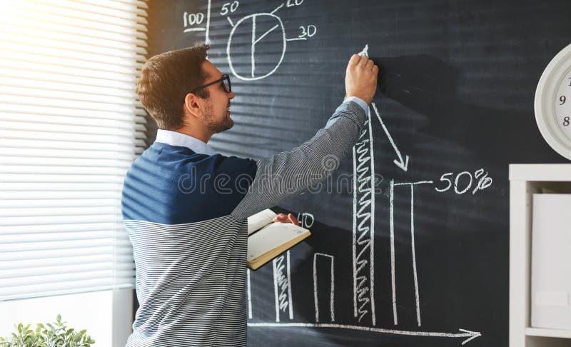 愉快的男学生,老师,有白垩的自由职业者在黑板 免版税库存图片