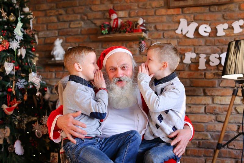 愉快的男孩兄弟在圣诞节的耳朵同时耳语 免版税库存照片