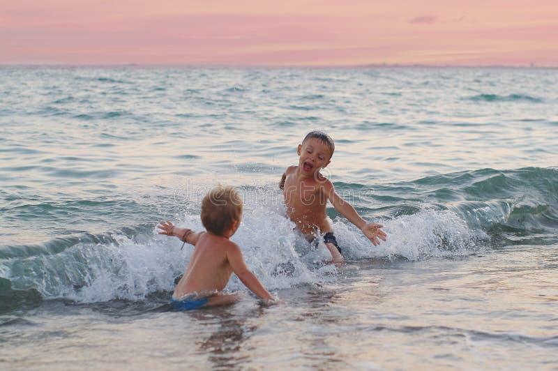 愉快的男孩充当在海滩的波浪 快乐的男孩在海波浪沐浴在日落 免版税库存图片